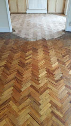 Parquet with dark varnish, having been partially sanded back.